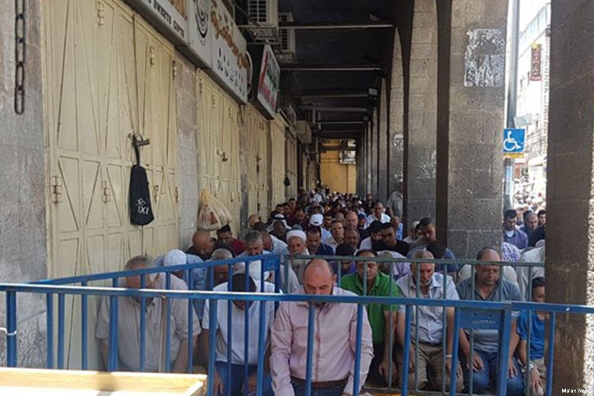 Worshippers take to the street to perform Friday prayers after Israeli forces closed down Al-Aqsa mosque on 14 July 2017 [Ma'an News]