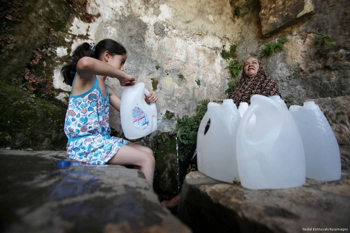 A Palestinian girl fills jerrycans with spring water in Salfit, West Bank on 27 June 2016 [Nedal Eshtayah/Apaimages]