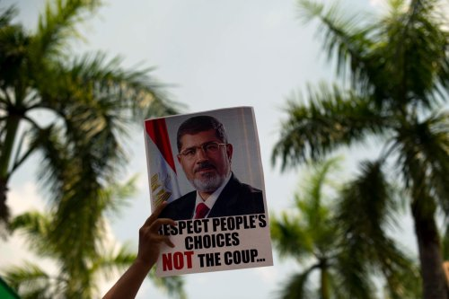 A protester holds a poster of ousted Egyptian President Mohamed Morsi during a rally to protest the Egypt's coup [MOHD RASFAN/AFP via Getty Images]