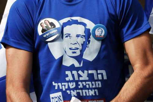 A supporter of the center-left Zionist Union wears a T-shirt showing Isaac Herzog, one of the party's leaders, outside a polling station in Tel Aviv in 2015. The Zionist Union was a joint electoral list by the Israeli Labor Party, Hatnuah and Green Movement. [Baz Ratner/Reuters]