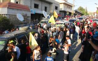 A convoy enters the village of al-Labweh in Baalbek district, Lebanon after Hezbollah and Jabhat Fateh al-Sham exchanged the corpses of fighters as part of a cease-fire between the two groups, on 30 July, 2017 [Suleiman Amhaz/Anadolu Agency]