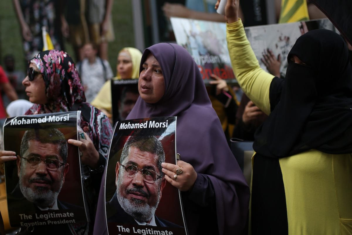 A woman holds a poster reading 'Mohamed Morsi, The Legitimate Egyptian President' during a protest marking the 4th anniversary of the Rabaa massacre in New York, US on 13 August 2017 [Mohammed Elshamy/Anadolu Agency]