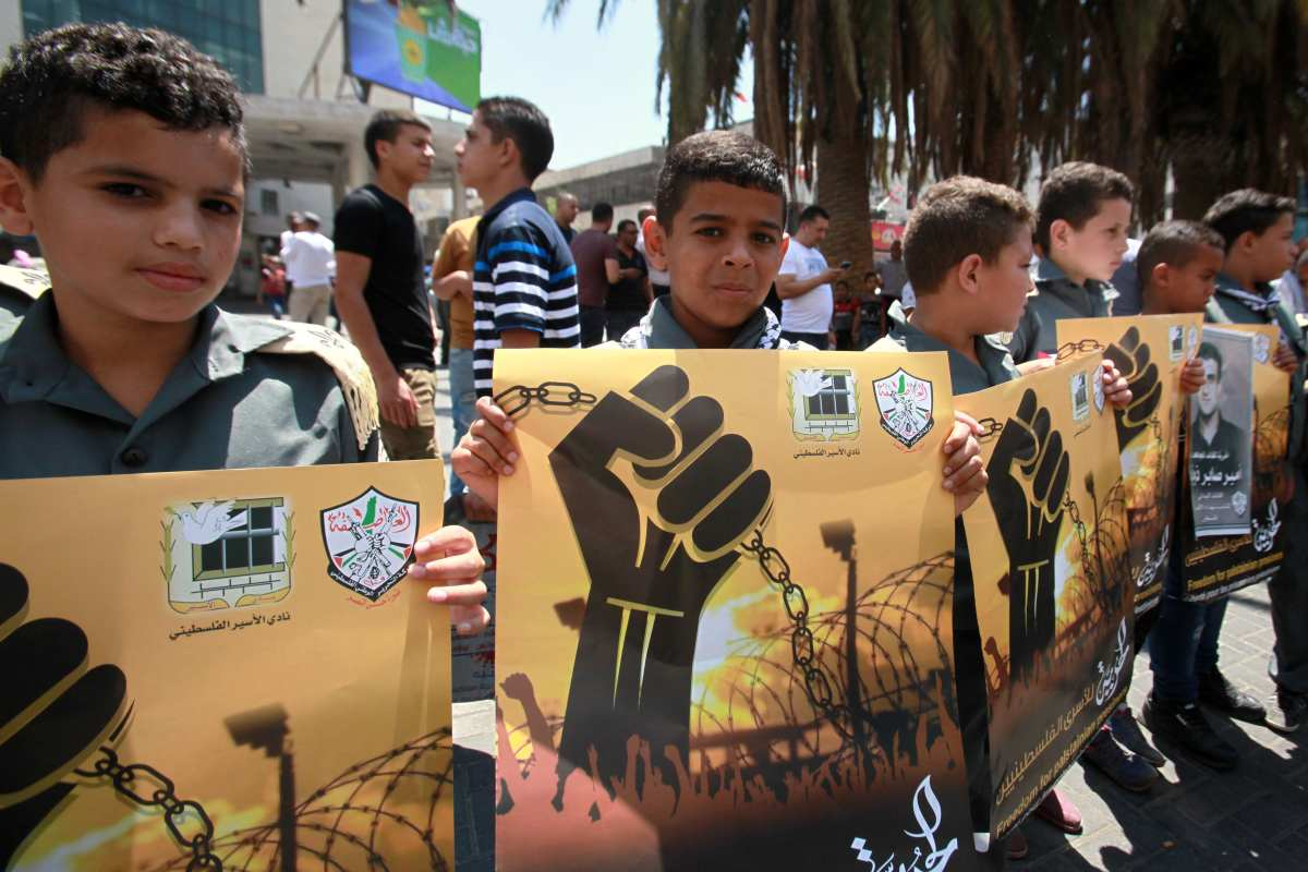 Palestinians gather to stage a demonstration organized by The Palestinian National Interest Committee as they hold a placard and Palestinian flags to support Palestinian prisoners in Israeli jails, in Nablus, West Bank on 14 August, 2017 [Nedal Eshtayah/Anadolu Agency]