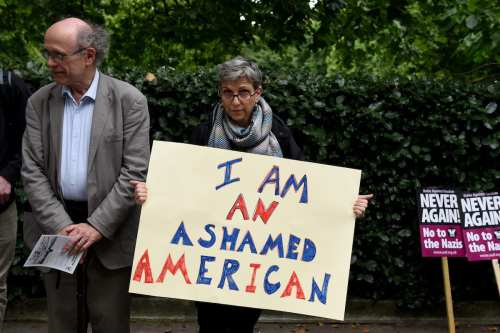 People gather to stage a demonstration as they hold placards during the 'Stand up to Racism' protest outside the US Embassy in London on 14 August, 2017 [Kate Green/Anadolu Agency]