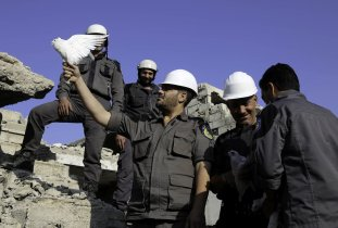 Men, members of Syrian civil defense organization, White Helmets let a white pigeon to fly for people who lost his life in chemical attack that in the Eastern Ghouta region of Damascus, Syria on 22 August, 2017 [Amer Almohibany/Anadolu Agency]