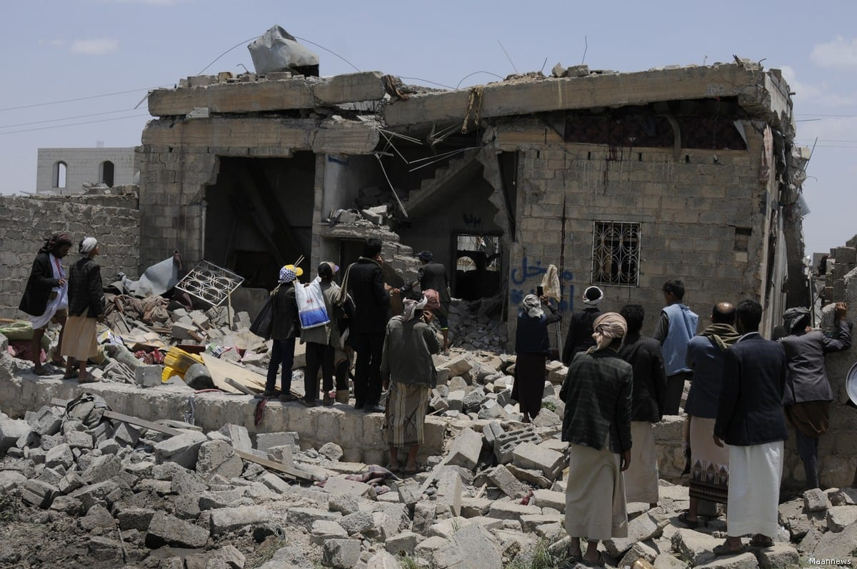 People gather around a heavily damaged building after Saudi-led coalition's air strikes over Arhab District of Sanaa, Yemen on 23 August, 2017 [Mohammed Hamoud/Anadolu Agency]