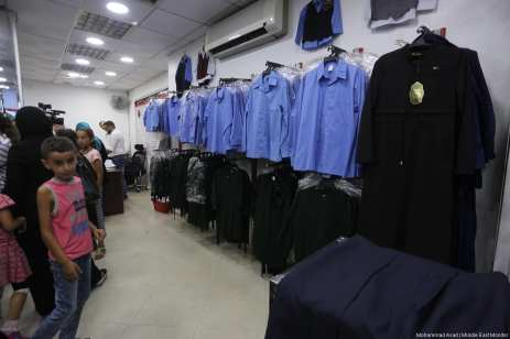 School uniforms are made and hung ready to be purchased for the new school year. [Image: Mohammad Asad / Middle East Monitor]