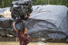 A Rohingya Muslim woman, fled from ongoing military operations in Myanmar's Rakhine state, carries plastic bags over her head at a refugee camp in Cox's Bazar, Bangladesh on September 20, 2017 [Safvan Allahverdi / Anadolu Agency]