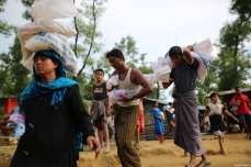 Rohingya Muslims carry sacks at a makeshift camp in Teknaff, Bangladesh on September 23, 2017 [Zakir Hossain Chowdhury / Anadolu Agency]