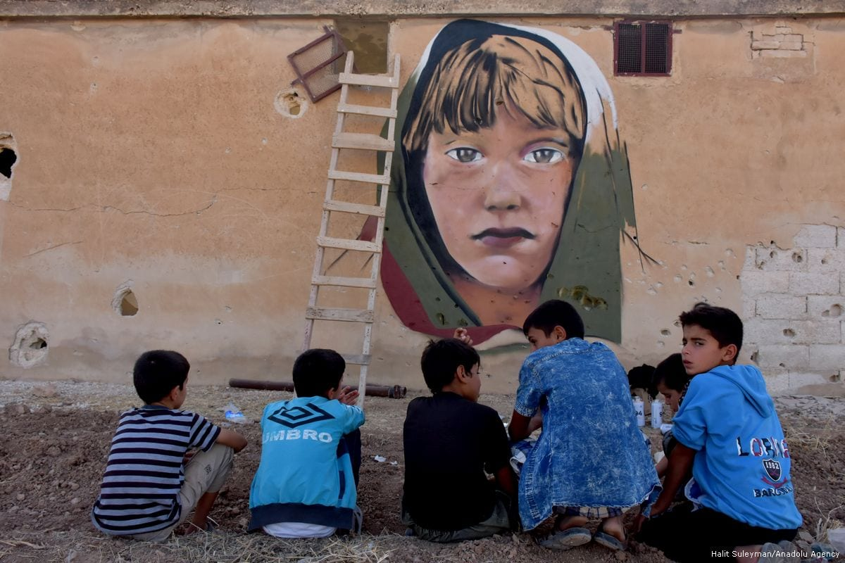 Children sit in front of a damaged wall decorated with an anti-war mural by a Turkish graffiti artist in Aleppo, Syria on 26 September 2017 [Halit Süleyman/Anadolu Agency]