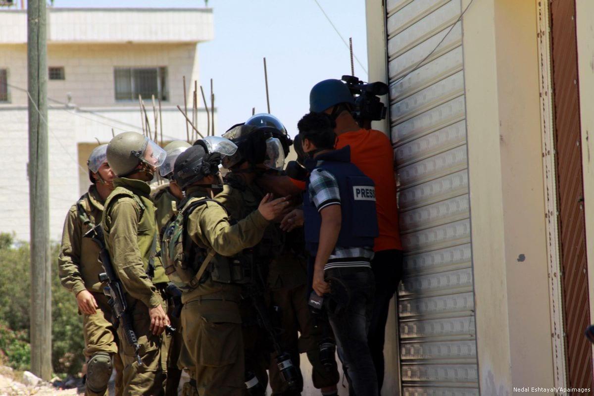 Israeli soldiers arrest Palestinian journalists during a protest against settlements [Nedal Eshtayah/Apaimages]