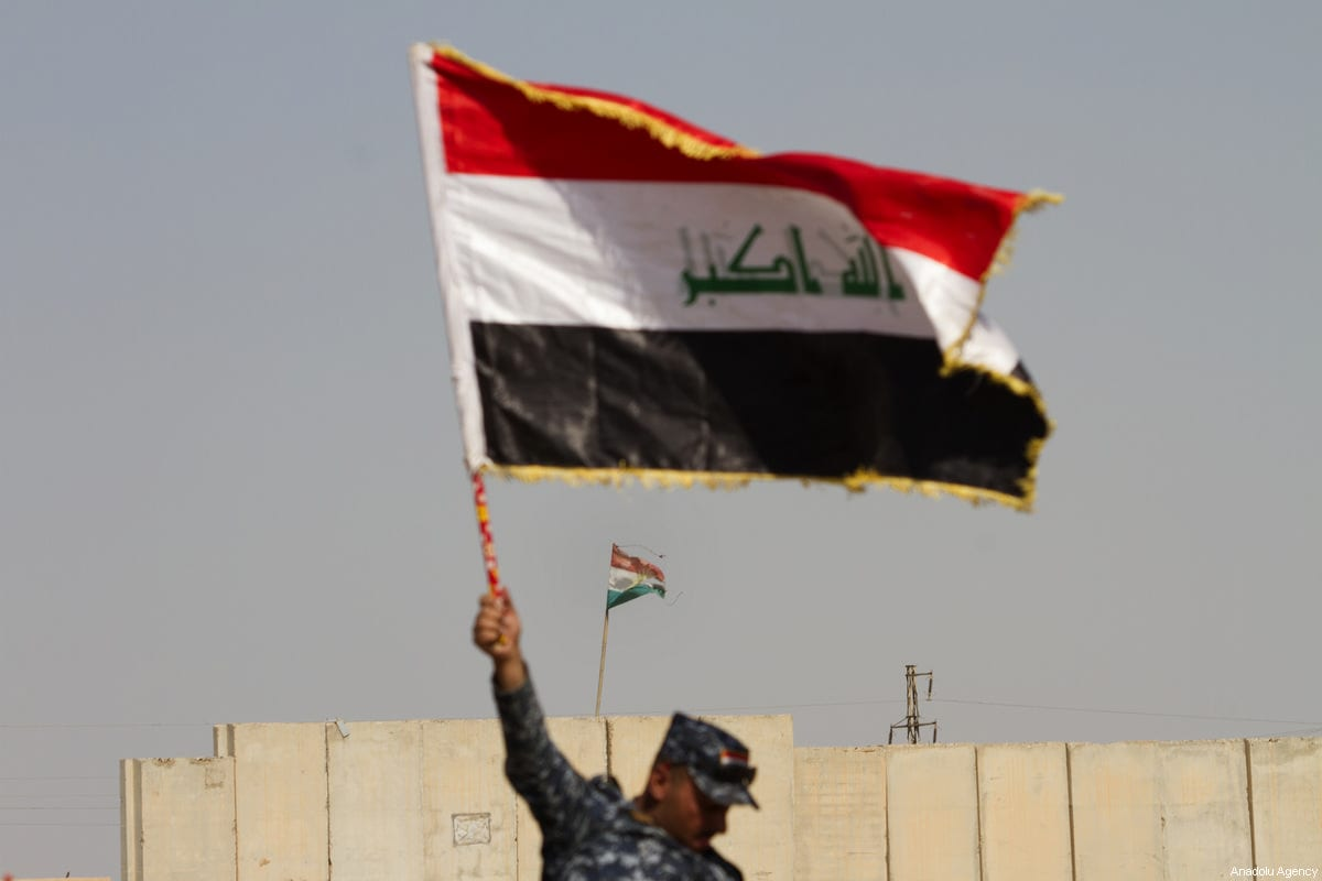 A member of Iraqi security forces waves an Iraqi flag meters away from the Peshmerga site in Kirkuk, Iraq on October 14, 2017. Iraqi security forces continue to deploy troops at southern Kirkuk as tension between Hashd al-Shaabi fighters and Peshmerga increases. [Hassan Ghaedi/Anadolu Agency]