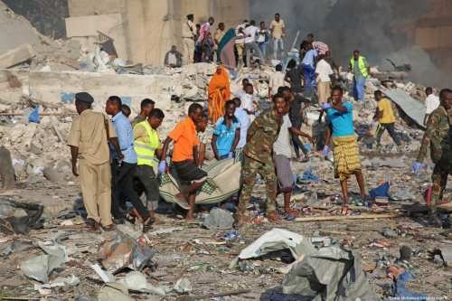 People carry bomb attack victims from the scene in the capital Mogadishu, Somalia on October 14, 2017. At least 23 people have died and many others injured after a truck bomb detonated in Mogadishu. ( Sadak Mohamed - Anadolu Agency )