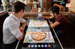 Customers selects his food served by robot waiter, which moves on rail system placed between tables. All services including payment, placing an order, are provided automatically via tables, which turn to digital screens like an tablet computer, at 'RoboChef' [Fatemeh Bahrami/Anadolu Agency]