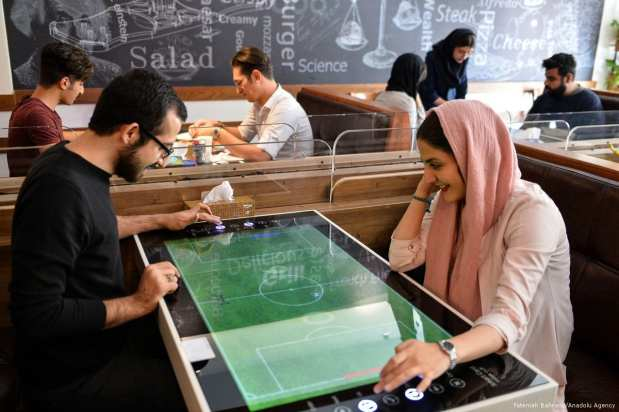 Customers play tennis as they wait for their food. All services including payment, placing an order, are provided automatically via tables, which turn to digital screens like an tablet computer, at 'RoboChef' [Fatemeh Bahrami/Anadolu Agency]