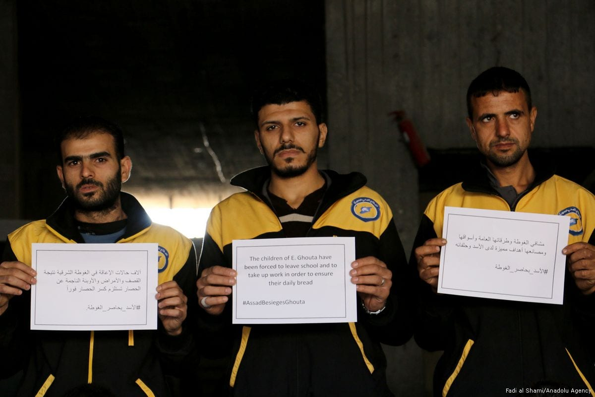 """The White Helmets hold banners as they stage a protest named """"Assad besieges Ghouta"""" to draw attention the deaths of children due to malnutrition on 26 October 2017 [Fadi al Shami/Anadolu Agency]"""