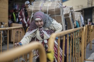 A porter heads towards the Spanish and Moroccan border while carrying bundles of goods on her back [Fernando Del Berro]