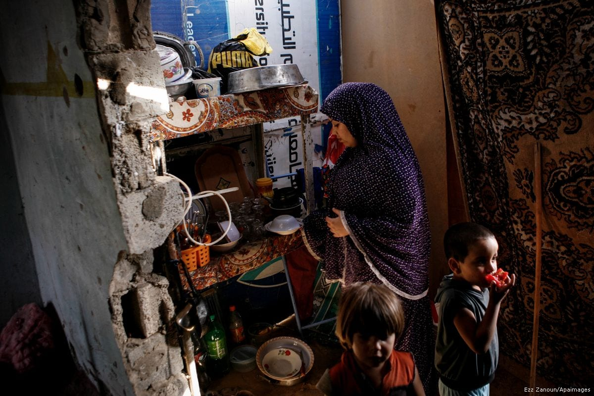 A Palestinian woman prepares food for her children at her home in a poverty-stricken quarter of al-Zaytoon in Gaza City on 17 September 2013 [Ezz Zanoun/Apaimages]