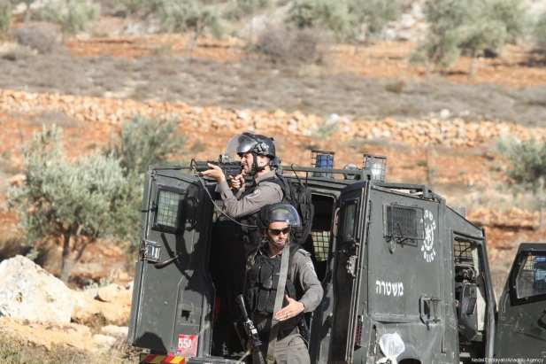 Israeli soldiers are seen as Palestinians react to Israeli soldiers after a Palestinian farmer shot dead by Jewish settlers, at the Khusra village of Nablus in West Bank on November 30, 2017. After that, Palestinians detained Jewish settlers in a cave and Israeli soldiers arrived at the scene and received these detained Jewish settlers. ( Nedal Eshtayah - Anadolu Agency )