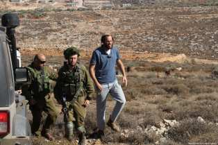 A Palestinian man reacts to Israeli soldiers after a Palestinian farmer shot dead by Jewish settlers, at the Khusra village of Nablus in West Bank on November 30, 2017. After that, Palestinians detained Jewish settlers in a cave and Israeli soldiers arrived at the scene and received these detained Jewish settlers. ( Nedal Eshtayah - Anadolu Agency )