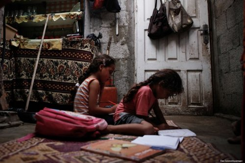 Palestinian children can be seen doing their homework in their makeshift home in one of the poorest neighbourhoods in Gaza [Ezz Zanoun/Apaimages]