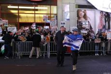 A man holds a Israeli flag as people attend a demonstration against US President Donald Trump's recognition of Jerusalem as Israel's capital, at the Times Square in New York City, United States on December 09, 2017 [Atılgan Özdil / Anadolu Agency]
