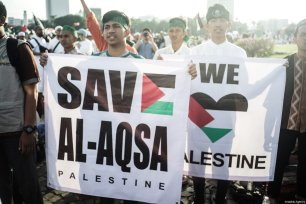 "Protesters show a banner reading ""Support Al-Aqsa and Palestine"" in the demonstration to support Palestine at National Monument in Jakarta, Indonesia on December 17, 2017 [Nani Afrida / Anadolu Agency]"
