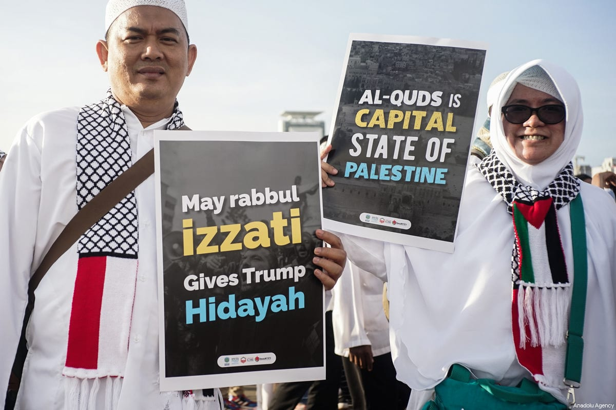"""Protesters show posters reading """"Let Trump get englightment and Al-quds is Palestine capital"""" in the demonstration to support Palestine at National Monument in Jakarta, Indonesia on December 17, 2017 [Nani Afrida / Anadolu Agency]"""