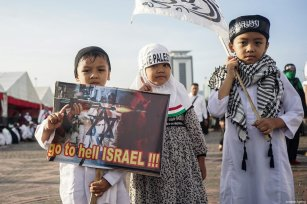 "Child protesters show a poster reading ""Israel go to hell"" poster and save Palestine headscarf in the demonstration to support Palestine at National Monument in Jakarta, Indonesia on December 17, 2017 [Nani Afrida / Anadolu Agency]"