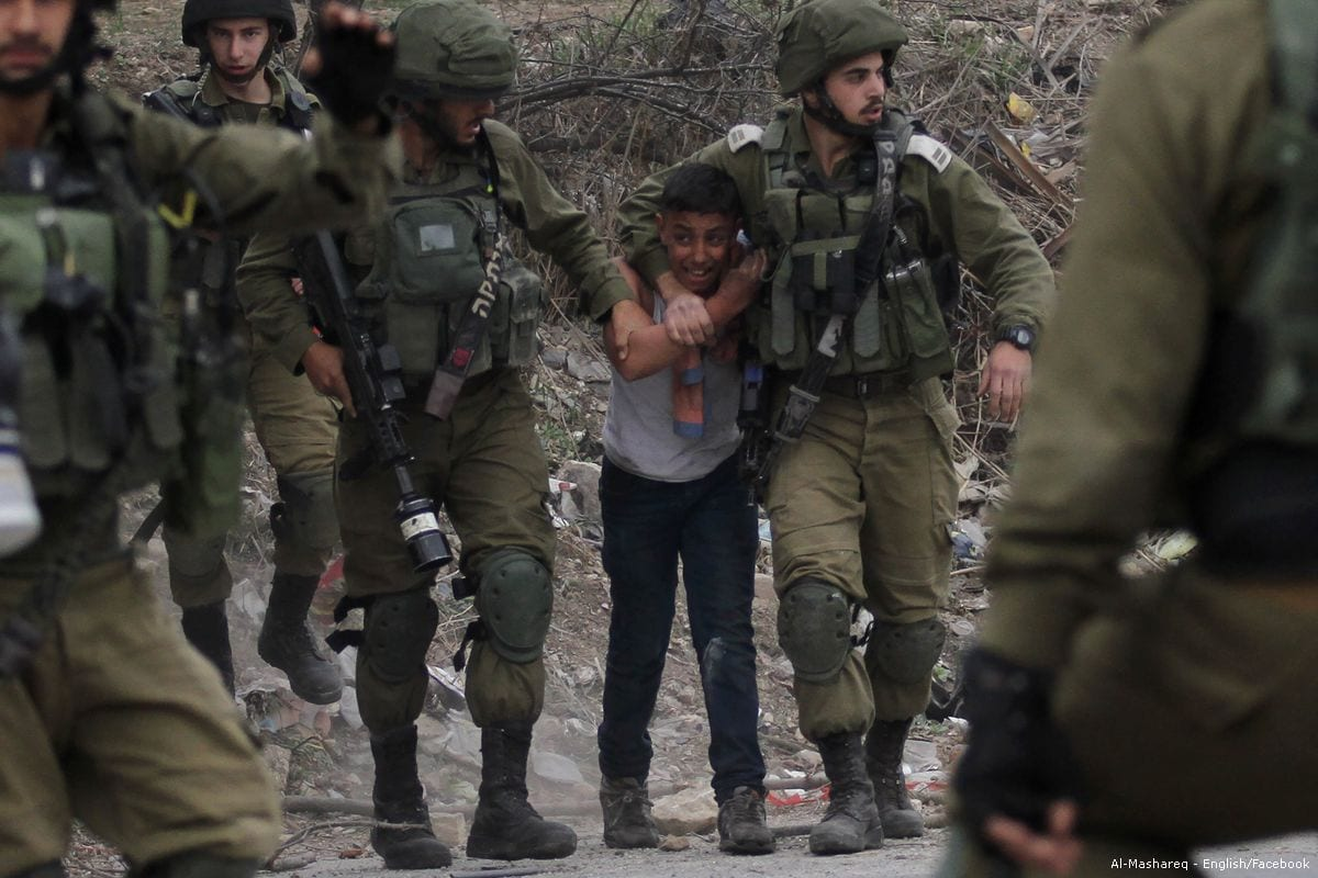 Israeli security forces arrest a Palestinian boy who was demonstrating against US President Donald Trump's announcement to recognise Jerusalem as the capital of Israel on 20 December 2017 [Nedal Eshtayah/Anadolu Agency]