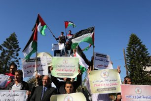 Palestinians wave the national flag during a demonstration to support the reconciliation in Gaza City on 3 December 2017 [Ashraf Amra/Apaimages]