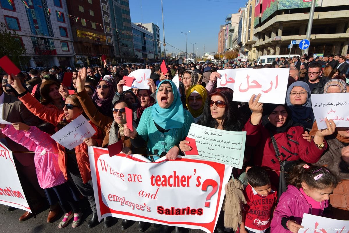 Thousands of public servants hold banners and shout slogans during a demonstration to protest non-payment of salaries and corruption at public enterprises, in Sulaymaniyah, Iraq on 18 December 2017 [Feriq Fereç/Anadolu Agency]