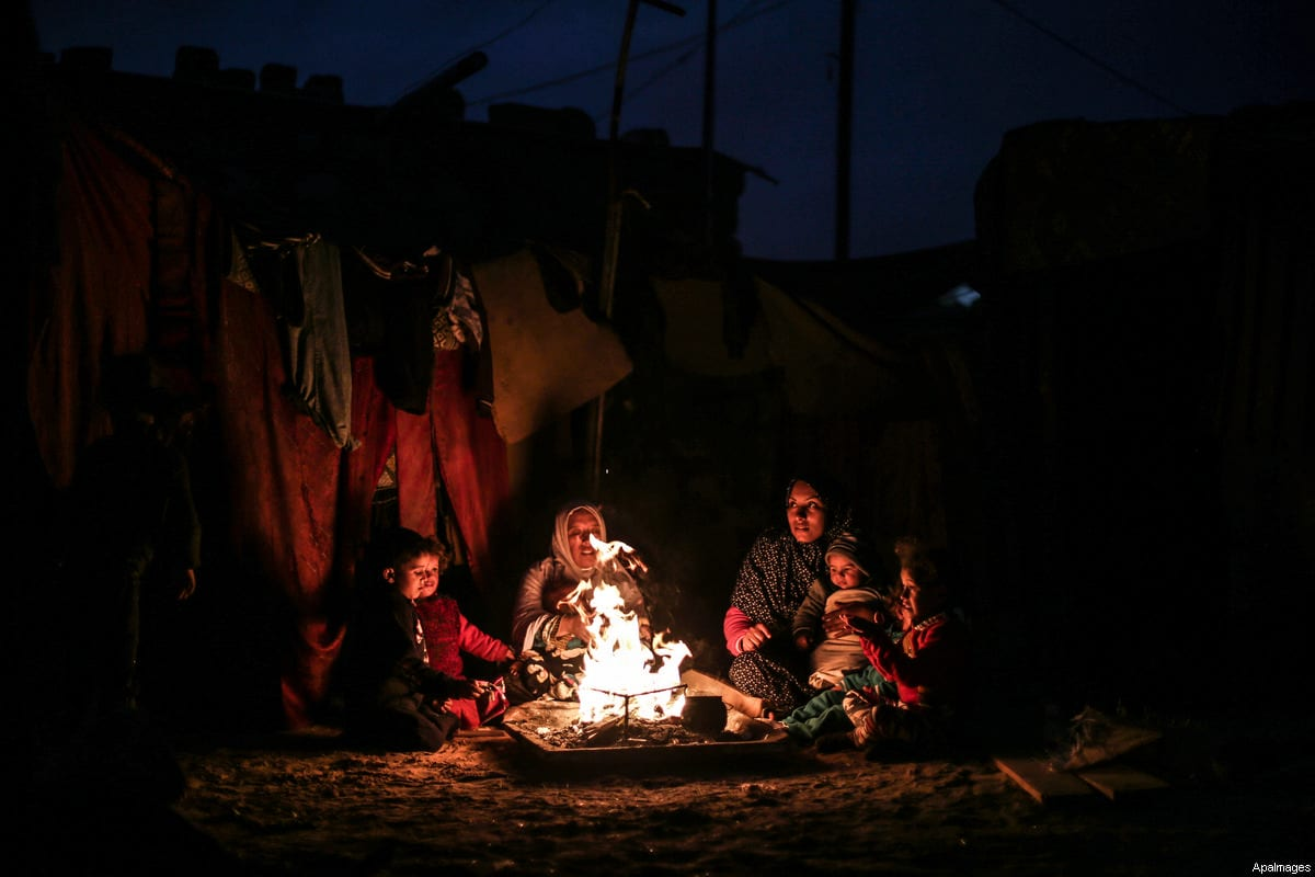 A Palestinian family warm themselves around the fire outside their dwellings during the power cut on winter season in Khan Younis, in the southern Gaza strip on January , 2017 [Mohammed Dahman / ApaImages]