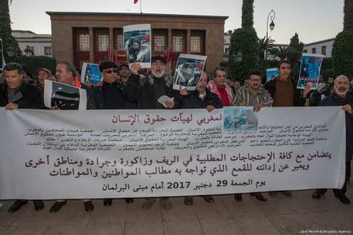 Demonstrators hold placards and a banner as they gather to protest, after two miners died while working in a coal mine in Jerada district, in front of the parliamentary building in Rabat, Morocco on 29 December, 2017 [Jalal Morchidi/Anadolu Agency]