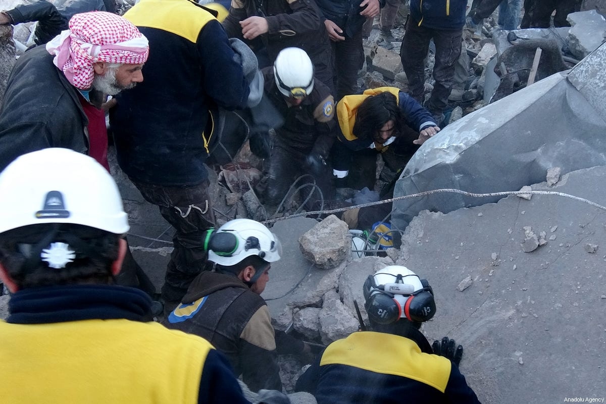Civil defense team members and citizens carry out search and rescue operation at the wreckage of a building after an airstrike to the de-escalation zone of Khan al-Sabil village in Idlib, Syria on January 02, 2018. ( Muaz Yemen - Anadolu Agency )
