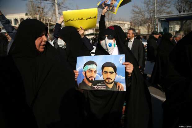 Iranians hold placards during a protest after performing the Friday Prayer at Imam Khomeini Mosque following US' statement about backing the anti-government protests in Tehran, Iran on January 05, 2018 [Fatemeh Bahrami / Anadolu Agency]