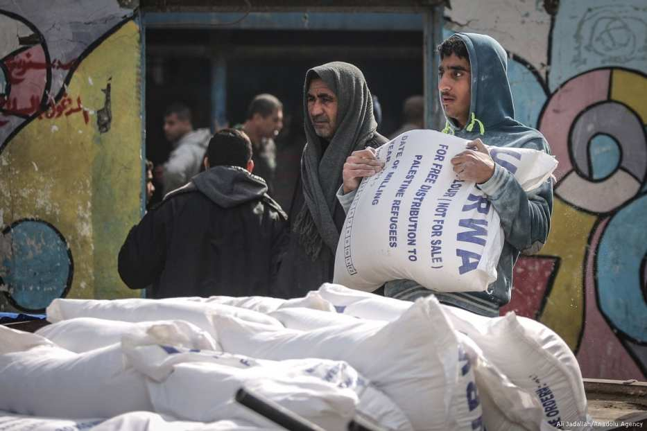 Palestinian men carry food aid given by UNRWA in Gaza City, Gaza on 15 January 2018 [Ali Jadallah/Anadolu Agency]