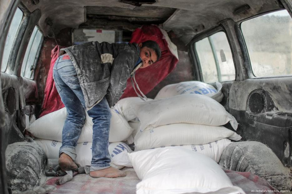 A boy is seen near sacks of flours in a car during a food aid distribution by the United Nations Relief and Works Agency for Palestine Refugees in the Near East (UNRWA) at Al-Shati Refugee Camp in Gaza City, Gaza on 15 January 2018 [Ali Jadallah/Anadolu Agency]