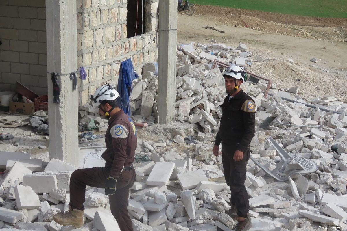 Syrians inspect the damage around the debris after an air strike hit Khan in Idlib, Syria [Muhammed Ali/Anadolu Agency]