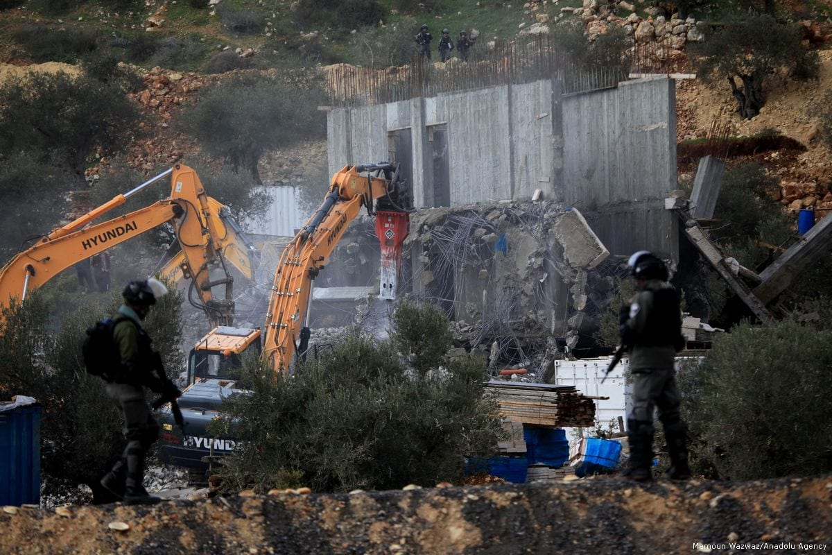 Bulldozers demolish two buildings belongs to Palestinians under the observation of Israeli forces in the West Bank on 29 January 2018 [Mamoun Wazwaz/Anadolu Agency]