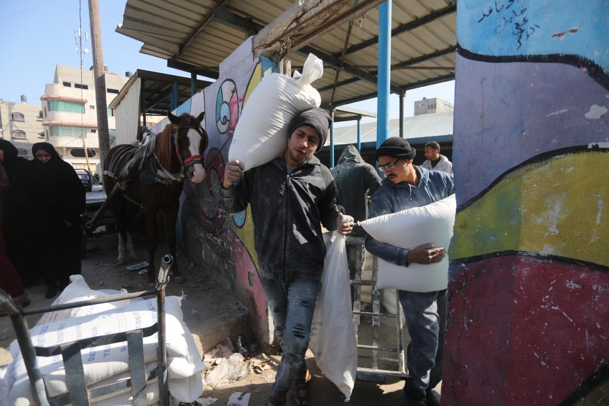 UNRWA beneficiaries seen collecting aid during a visit by Pierre Krähenbühl, commissioner-general of the UN Relief and Works Agency (UNRWA) to Gaza on Janaury 22, 2018 [Middle East Monitor / Mohammad Asad]