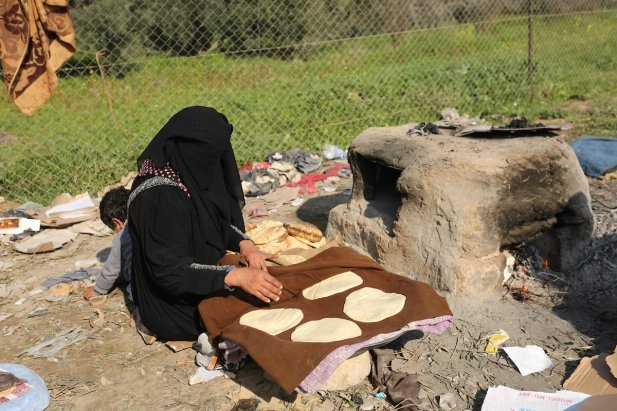 A Palestinian woman bakes bread in her neighborhood which experiences power shortages, in Johr El-Deek in Gaza on 1 February, 2018 [Ashraf Amra/Apaimages]
