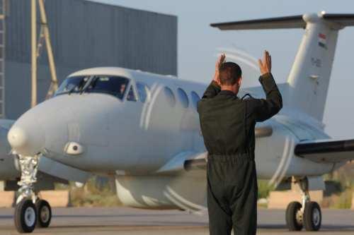 An Iraqi air force crew chief marshals a King Air 350 intelligence, surveillance and reconnaissance aircraft to the taxiway, at New Al Muthana Air Base, Iraq [US Air Force / Senior Airman Perry Aston]
