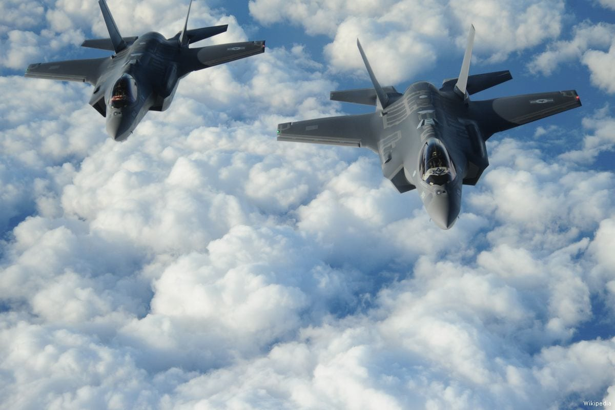 "Two US-made Israeli F-35 ""Adirs"" fly in formation, and display the US and Israeli flags, en route to Israel for their delivery on December 6, 2016 [U.S. Air Force/Wikipedia]"