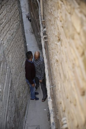 """Two Iraqi men pass each other on the narrowest alley in Baghdad, Iraq, which has 30 cantimeters width and 70 meters length and called """"derbune"""" by the local people, on 15 January, 2018 [Murtadha Sudani/Anadolu Agency]"""