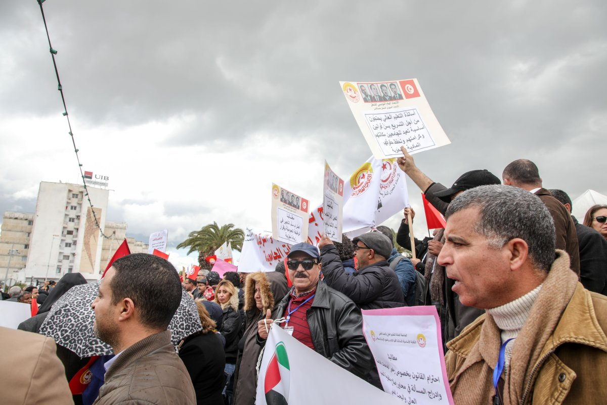 Tunisian academicians hold placards during a protest against price hikes demanding their wage's increase in front of parliamentary building in Tunis, Tunisia on 21 February, 2018 [Nacer Talel/Anadolu Agency]