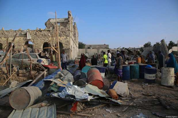 People inspect the site after two attacks carried out bomb-laden vehicles near Somalian National Intelligence and Security Agency (NISA) building in Mogadishu, Somalia on February 24, 2018 [ Sadak Mohamed / Anadolu Agency]