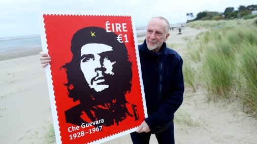 Irish artist Jim Fitzpatrick with a promotional image of a stamp featuring his world famous image of Che Guevara [Irish Times]