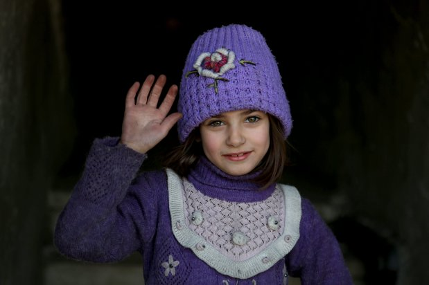 """A Syrian girl raises her hand as she poses for a photo for the awareness-raising campaign """"#Iamstillalive"""" on the social media, organized by activists and children, demanding support for the humanitarian crisis caused by Assad Regime and its supporters in Eastern Ghouta of Damascus, Syria on 2 March, 2018 [Amer Alshami/Anadolu Agency]"""