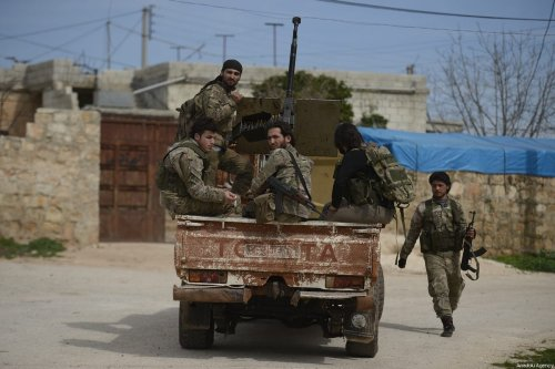 """Free Syrian Army members seen on the back of a truck, patroling an area after Turkish Armed Forces and FSA members cleared Kafr Rum village in the northeastern Sharan district from Daesh, as part of """"Operation Olive Branch"""" in Afrin, Syria on March 10, 2018 [Huseyin Nasir / Anadolu Agency]"""